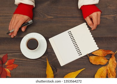 Hands of writer with a pen and notebook at a wooden table with a cup of espresso and autumn leaves