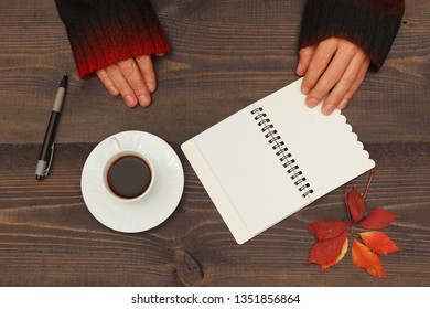 Hands of writer at a wooden table with a cup of espresso and a notebook with pen