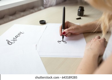 Hands writing with brush and ink, the lettering process. Concept creativity and calligraphy, light background, toning