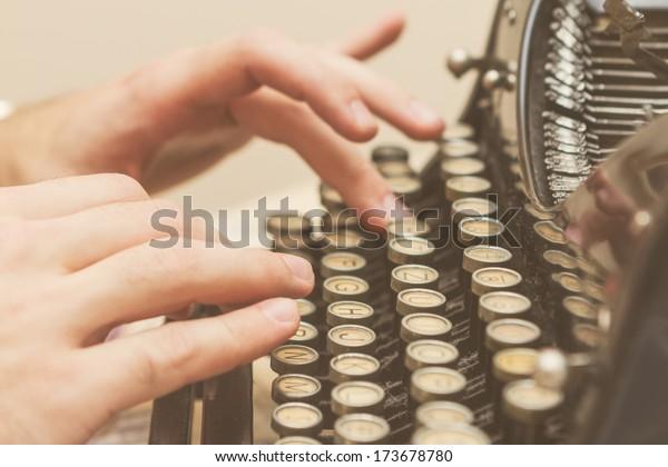 Escribiendo manos sobre una vieja máquina de escribir