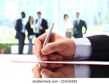 Hands writing on a paper while business people team work during conference