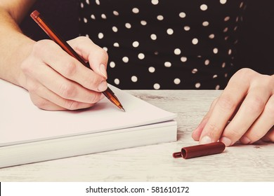 Hands writing something on the white paper.