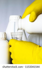 Hands in yellow gloves pour pesticides into a measuring glass.