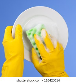 Hands in yellow gloves washing dish on blue background
