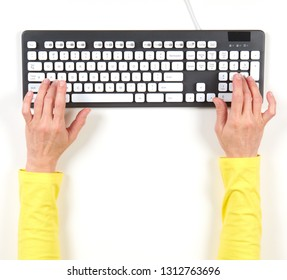 Hands in yellow jacket and grey keyboard on white background