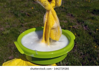 Hands in yellow protective gloves squeeze yellow rag.