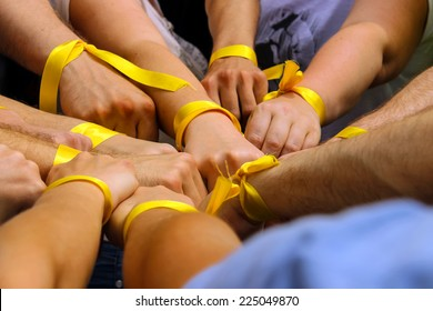 Hands with yellow ribbons together. The concept of the unity of sport