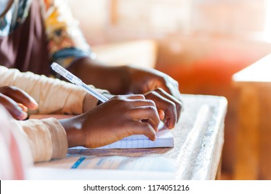 hands of young african school boys and girls during lesson in classroom with bright sun light holding pen and writing