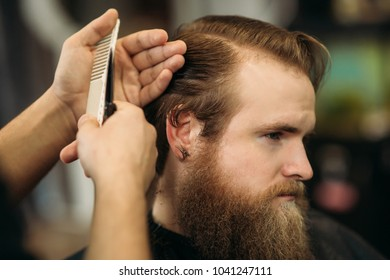 The hands of young barber making haircut to attractive bearded man in barbershop