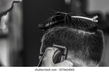 The hands of young barber making haircut of attractive bearded man in barbershop. Barbershop armchair. modern hairdresser and hair salon, barber shop for men. Black and white filter.
