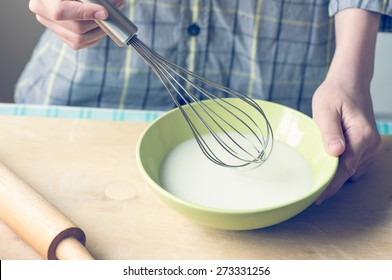 Hands of a young boy with a whisk and a bowl of baking