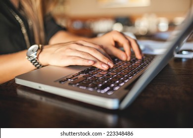Hands of young business woman in cafe drinking coffee with laptop indoor