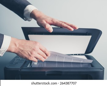 The hands of a young businessman is placing a document on a flatbed scanner in preparation for copying it