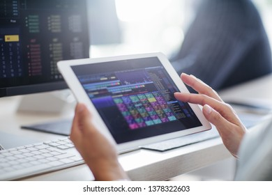 Hands of a young businesswoman using a tablet while working with stock market forecast.