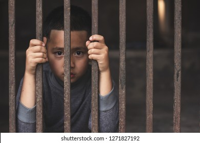 Hands of a young child clutching prison bars, victim child with locked in a cage cell, in emotional stress and pain, Children violence and abused concept.