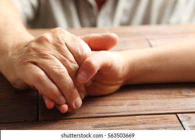 Hands of young child and old senior