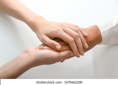 Hands of young and elderly woman on white background. Concept of support