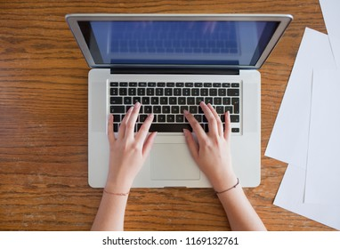 hands of young female person typing on laptop, blank paper sheets located nearby