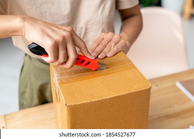 Hands of young female with stationery knife cutting sealed cellotape on top of packed cardboard box while standing by table during work