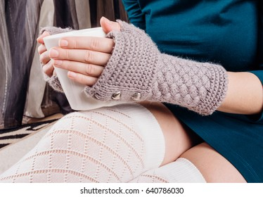 The hands of a young girl in gloves without a finger hold a white cup of tea