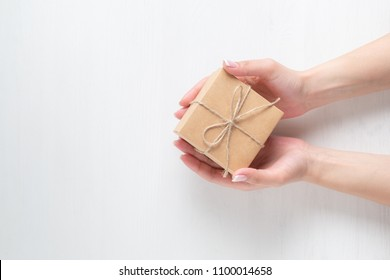 hands of a young girl opening a gift box on a white wooden background