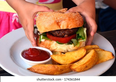 Hands of a young girl ready to eat a big hamburger. Concept photo of child obesity, unhealthy eating, unhealthy food.