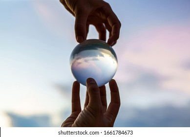 Hands of a young magician guy holding a glass ball for contact juggling at sunset