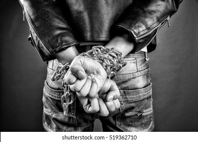 Hands of young man in chains on a gray background
