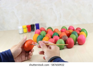 Hands of young man painting easter eggs with paintbrush on marble top with copy space background.