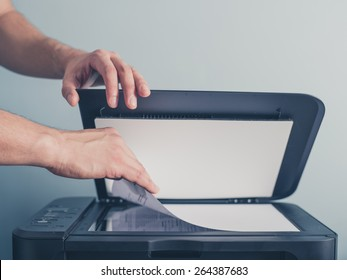 The hands of a young man is placing a piece of paper on a flatbed scanner in preparation for copying it