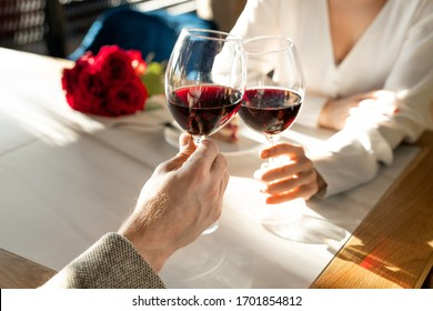 Hands of young man and woman with glasses of red wine over served table toasting for love during lunch in classy restaurant