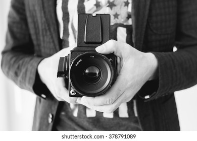 Hands of young photographer holding old medium format camera , black and white