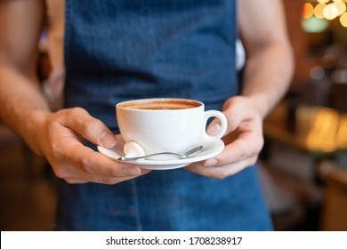 Hands of young waiter of classy restaurant carrying cup of fresh cappuccino with spoon and tiny meringue on saucer