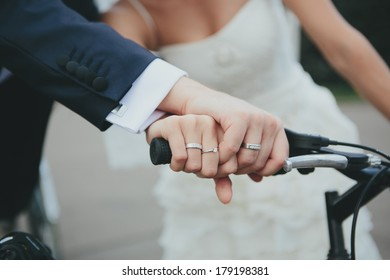Hands of a young wedding couple with rings holds together the bike handle