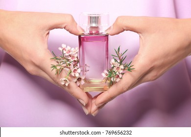 Hands of young woman with bottle of floral perfume, closeup