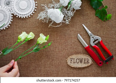 The hands of young woman florist making bouquet of flowers.