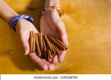Hands of a young woman with cinnamon sticks
