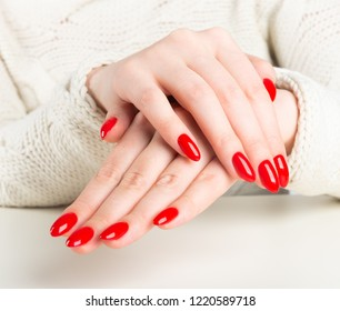 hands of a young woman with dark red manicure