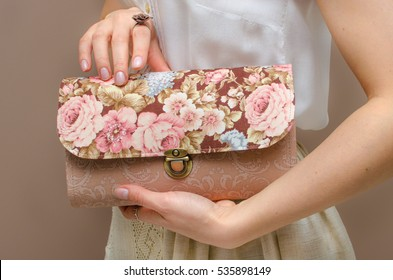 In the hands of a young woman dressed in white cotton blouse and beige linen skirt, a delicate clutch bag with floral print of roses on a brown background. Women's day, fashion, spring, romance, love.