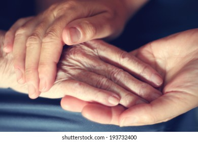 Hands of young woman and elderly woman