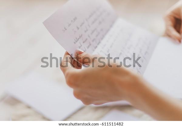 Mains d'une jeune femme tenant une lettre manuscrite