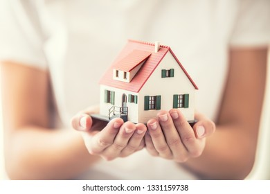 Hands of young woman holding model house.