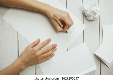 Hands of young woman holding a pen, a handwritten letter and a crumpled paper sheet