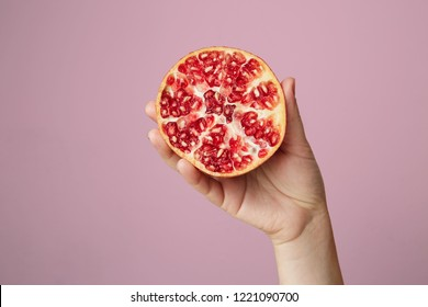 Hands of a young woman holding a red pomegranate. healthy food concept over pink background