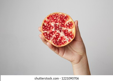 Hands of a young woman holding a red pomegranate. healthy food concept over gray background