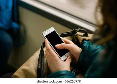 hands of a young woman holding a white smart phone tapping the blank screen in a bus
