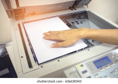 The hands of a young woman is placing a piece of paper on a flatbed scanner in preparation for copying it.