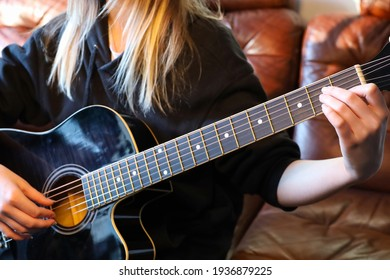 Hands of a young woman playing a black guitar.