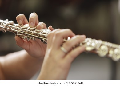 Hands of young woman playing the flute