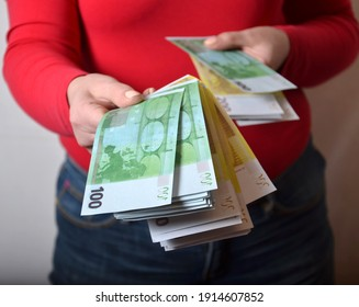 The hands of a young woman in a red blouse and jeans, holding a wad of euro banknotes. Close-up, studio shot.